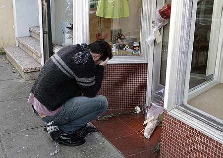 Peter Helmenstine weeps at the storefront of the department store Doe, which is owned by the Kim family, Wednesday, Dec. 6, 2006, in San Francisco. (AP)