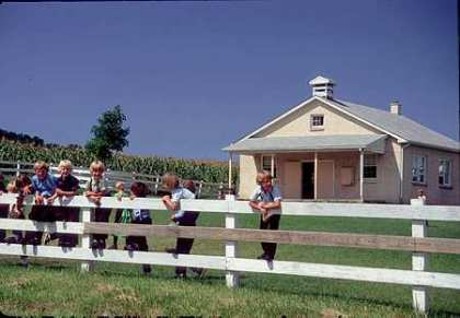 Above, children are shown at Nickel Mines School on a happy day. The year was 1990. In photo below, Amish gather Thursday morning before dawn to watch the school, the site of a massacre on Oct. 2, be torn down. The building is gone, but not forgotten. (Lancaster Newspapers file photo)